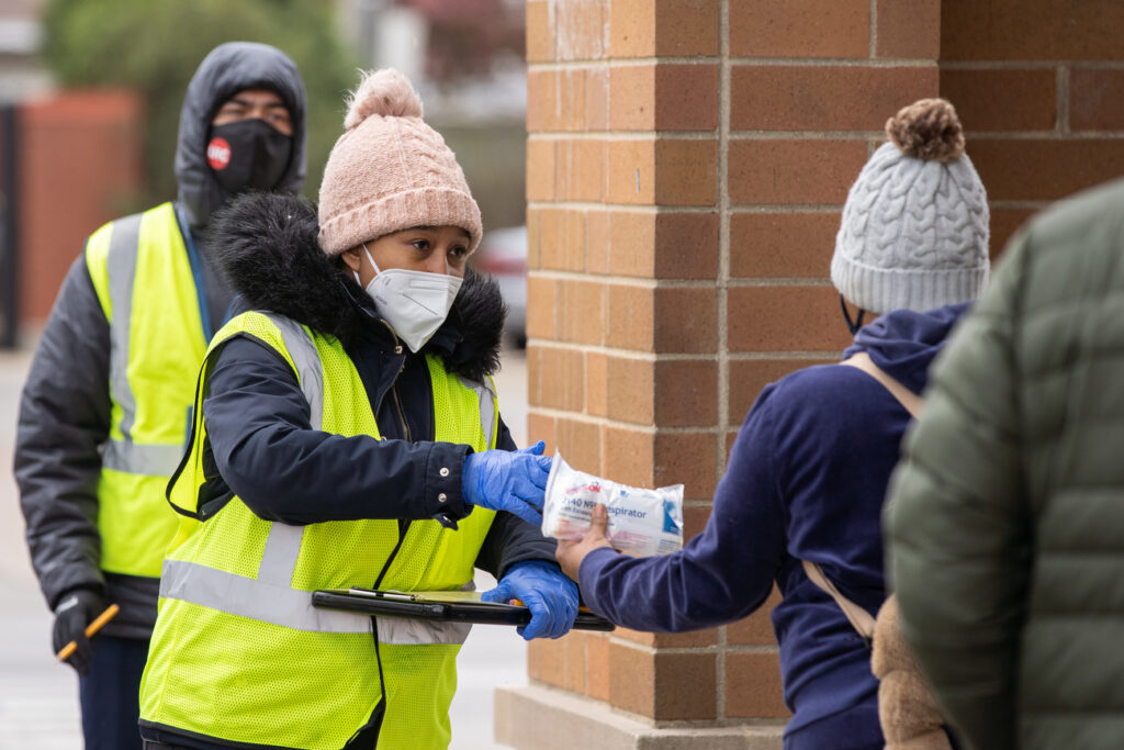 A COVID-19 outreach specialist hands out masks